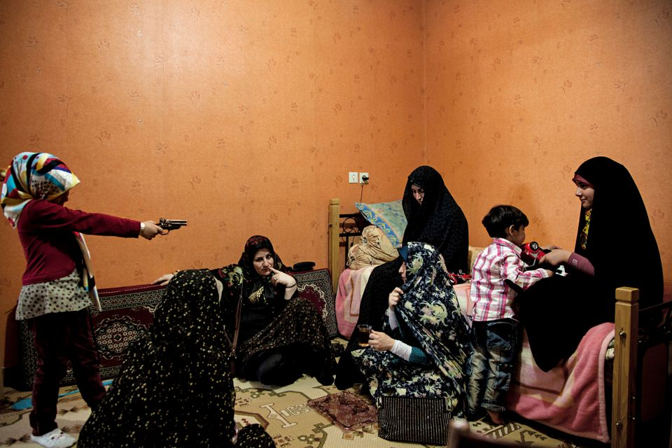 Women talk as a little girl plays with a toy gun during a religious celebration. In traditional families men and women gather