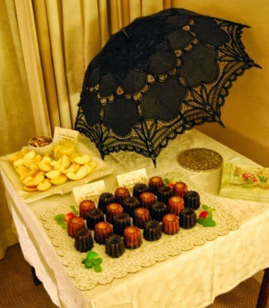 Here, for example a black parasol becomes a table decoration accompanied by various nibbles.   Or, a top hat becomes a table