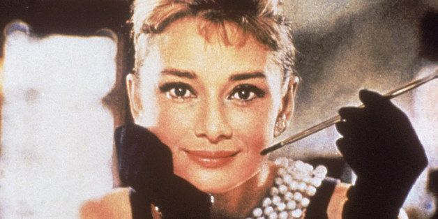 Belgian-born actress Audrey Hepburn (1929 - 1993), in a black, shoulderless dress, matching gloves, and a tiara, smiles with