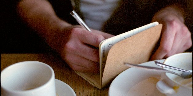 A writer sits in a cafe surrounded by teacups. He is writing in a notebook. The shot is a close up of his hands.