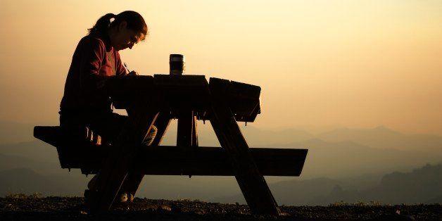 Woman sitting at a picnic table.