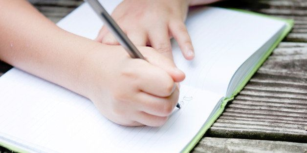 Hands of a young child, writing in their journal