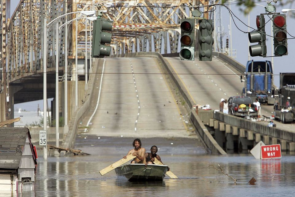 Two men paddle in high water after Hurricane Katrina devastated the area August 31, 2005 in New Orleans, Louisiana. Devastati