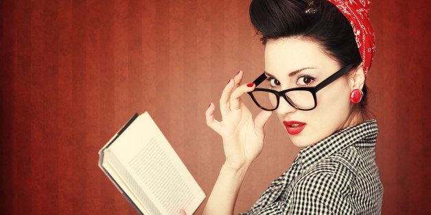 Portrait of a retro colored young brunette, reading an exciting book, looking at camera, in vintage clothes and glasses.