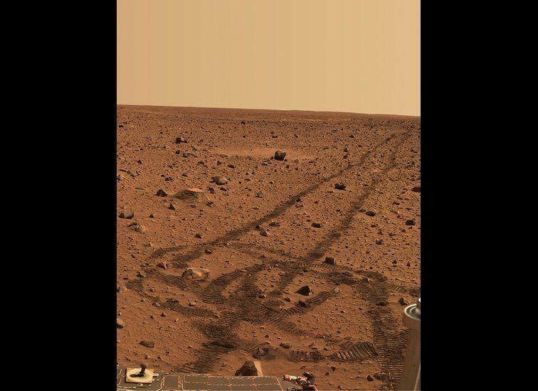 While driving over the reddish rocks and soils of Mars, the rover's wheels dig below the thin