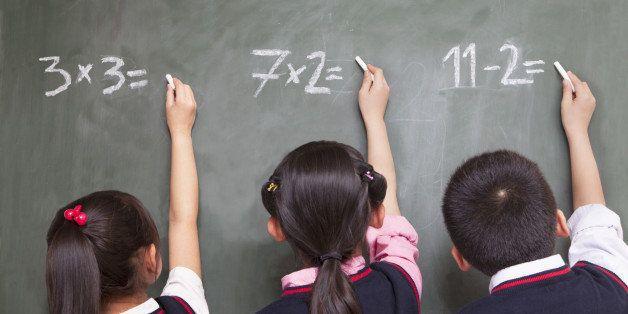 Three school children doing math equations on the blackboard
