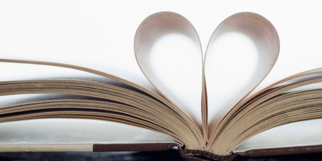 Close-up of book on beach with pages folded in heart shape