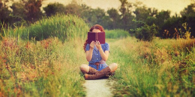 Young woman with long red hair wearing short-sleeved blue and white dress with brown belt and mid-calf brown leather boots sits cross-legged on narrow dirt footpath through field and holds up old brown book with both hands, obscuring face. The background is in shallow focus and overlaid with old paper texture.
