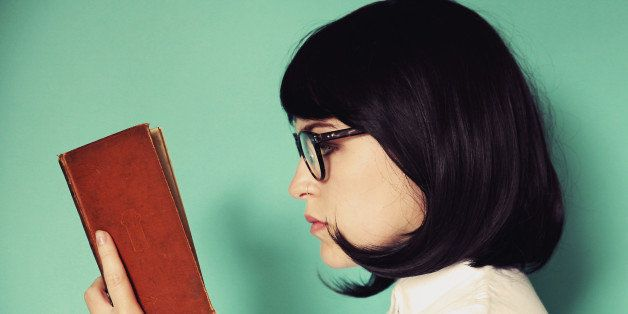 Profile of a young woman reading a book wearing glasses