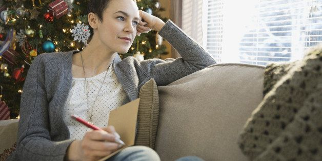 Thoughtful woman writing in Christmas cards at home