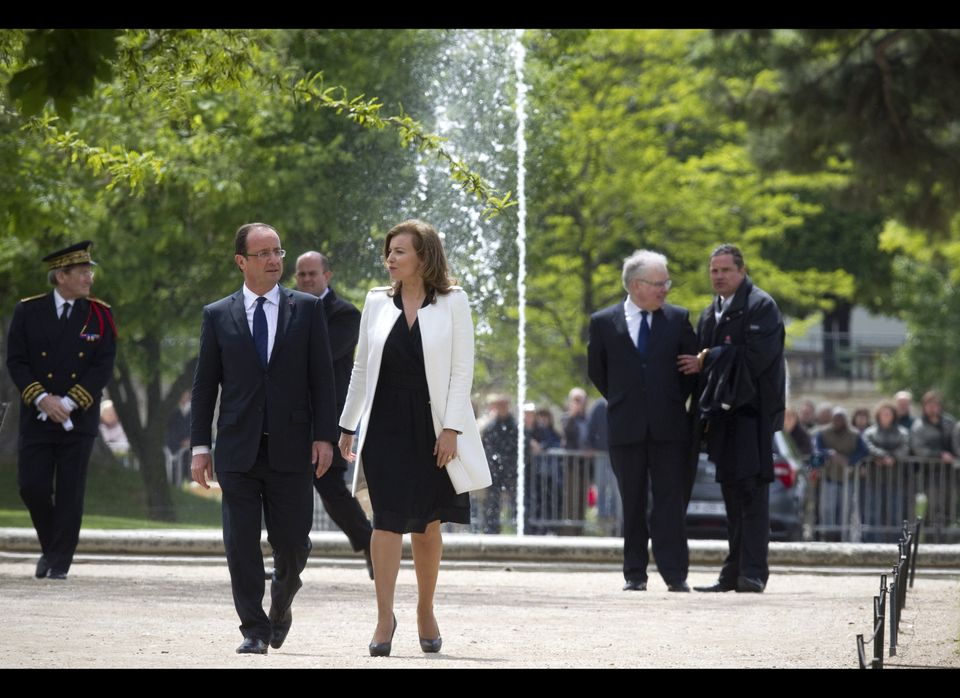 France's President Francois Hollande (C,L) and his companion Valerie Trierweiler (C,R) arrive at the Tuileries Garden in Pari