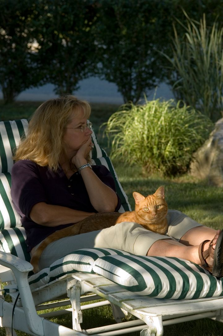Woman with cat relaxing on a chaise lounge on a summer day.