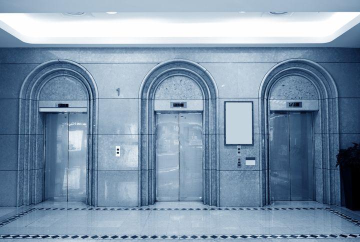 three elevator doors in...