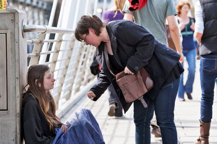 LONDON-APRIL 25: A unidentified woman gives money to a young homeless woman on Charing Cross Bridge on April 25, 2010 in Lond