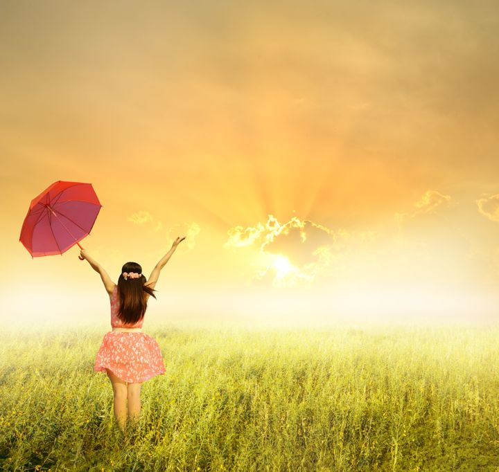 Beautiful woman holding red umbrella in  grass field and sunset