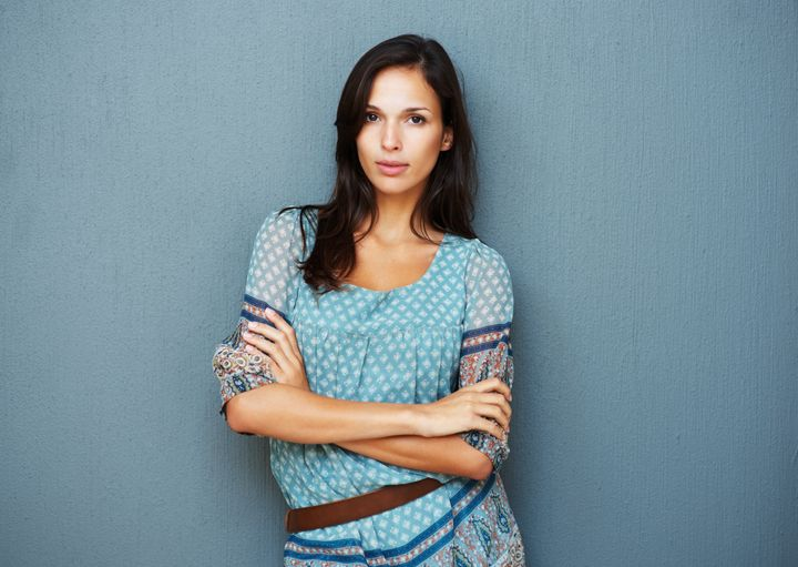 Earnest woman with arms crossed against a blue background
