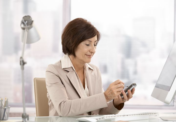 Mature female executive using smartphone in office, smiling.?