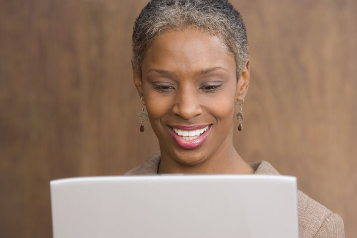 Close up of mid adult businesswoman with laptop