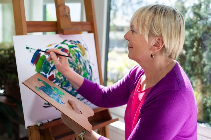 happy retired woman painting on ...
