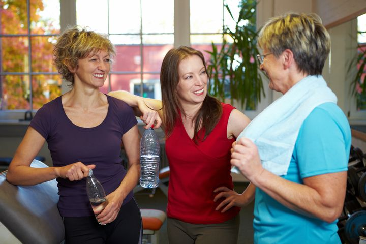 Happy elderly women talking in a gym
