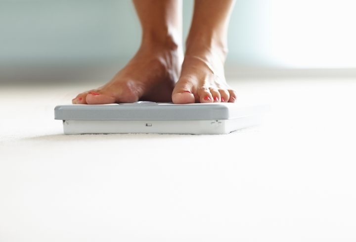 Low section closeup of a woman's feet on weighing scale