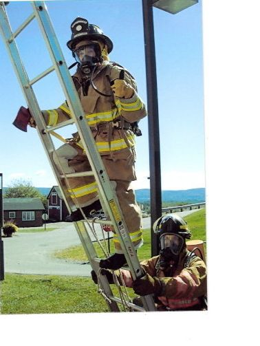 Andrea Peterson is on the ladder, wearing 60 pounds of firefighter gear.