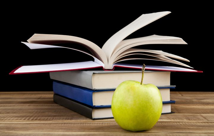 apple and books on wooden table