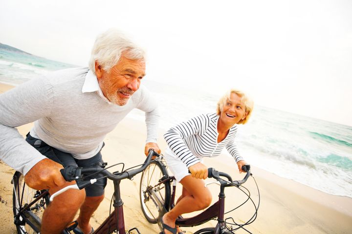 Senior couple driving bicycles on the beach