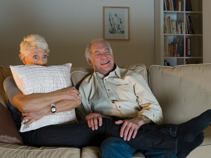 A senior couple watching tv