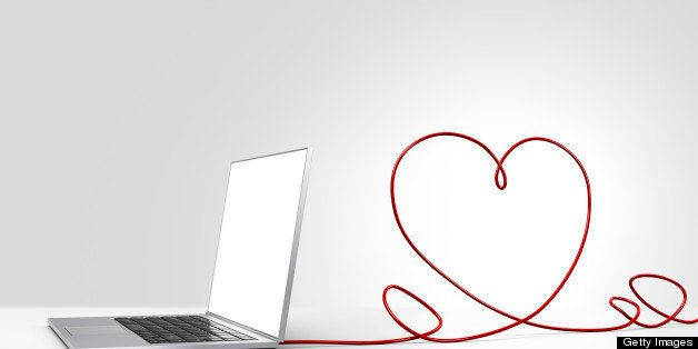 Laptop computer with a red ethernet cable forming a heart, coming out of the back on a plain background
