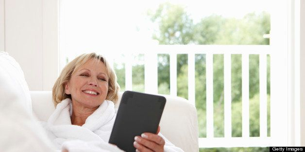 Woman reclining on sofa using digital tablet