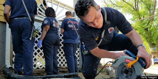 CAPITOL HEIGHTS, MD - APRIL 27: Lt. J.P.Callan uses an electric saw to cut lattice for the front porch of the Lowman family h