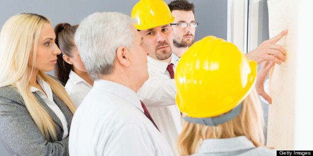Business people discuss the project with colleagues and contractors.