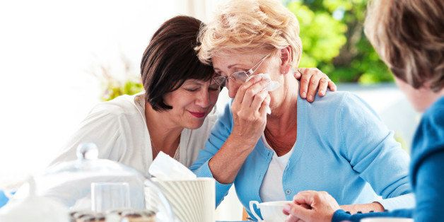 Senior women sitting at the table at home and comforting ther unhappy friend.