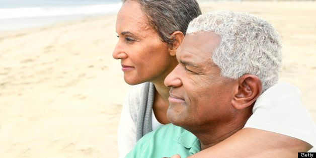 A happy senior couple is sharing a romantic moment on the beach.