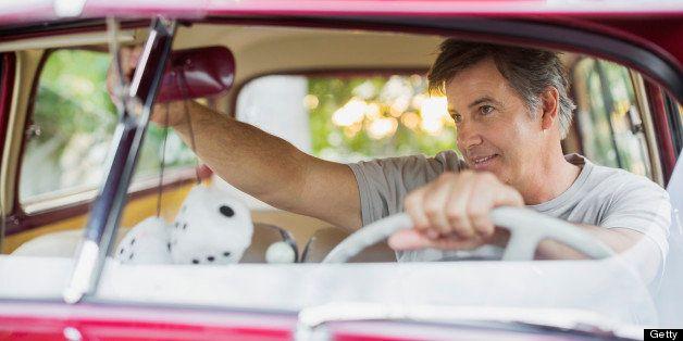 Senior man adjusting rear-view mirror in vintage car