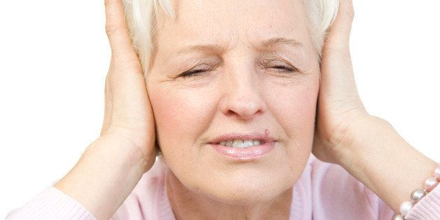Old woman covering her ears with both hands