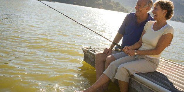 Mature couple by lake fishing
