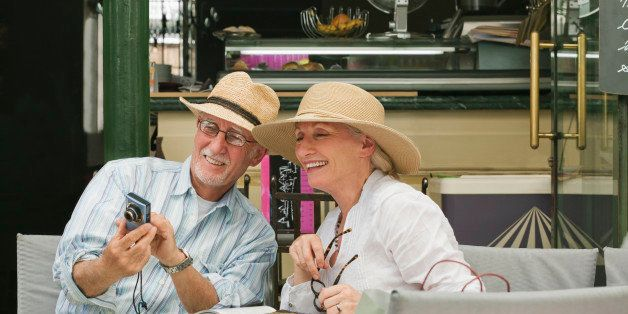 Mature couple seated in sidewalk cafe sharing photos of their trip.