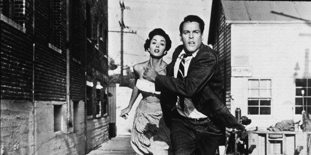 Becky Driscoll (German-born actress Dana Wynter) and Dr. Miles Bennell (American actor Kevin McCarthy) hold hands and run fro