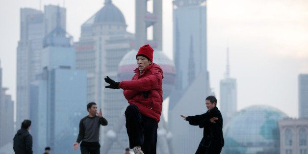 People practice Tai Chi on the Bund as commercial buildings stand in the Pudong area, background, in Shanghai, China, on Tues