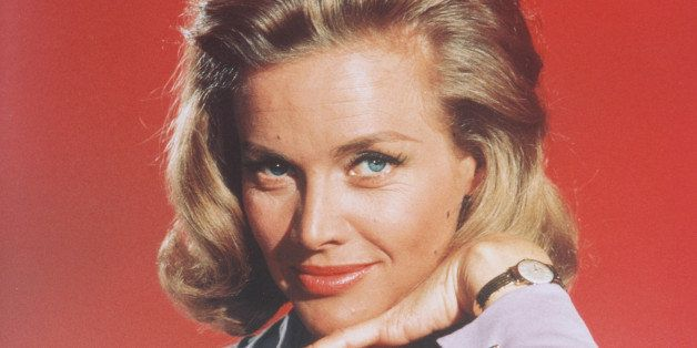 Honor Blackman, British actress, posing in a studio portrait, aginst a red background, issued as publicity for the film, 'Gol