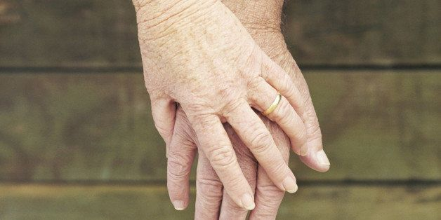 Elderly couple holding hands, close-up