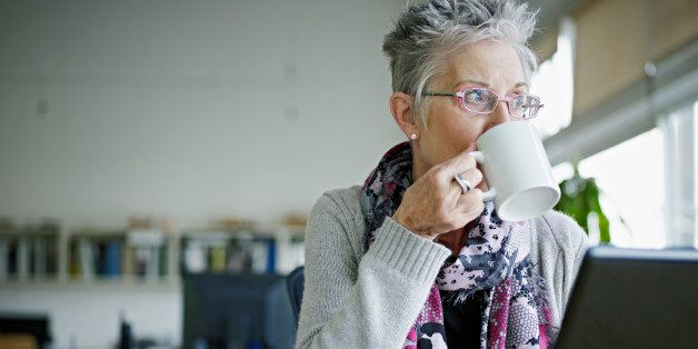 Businesswoman sitting at laptop in office drinking coffee looking out window
