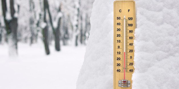 thermometer in the snow with temperature below zero degree Celsius