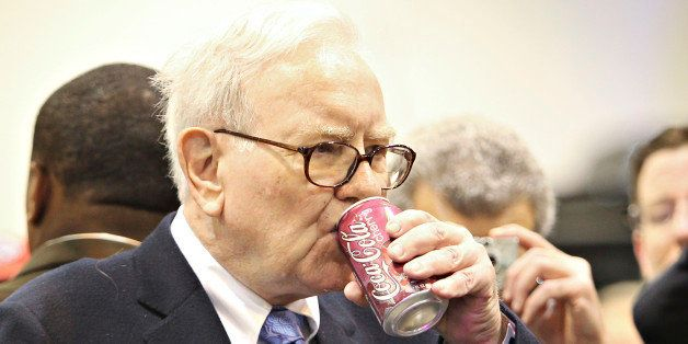 Warren Buffett, chief executive officer of Berkshire Hathaway, drinks a Cherry Coca-Cola as he tours the exhibition floor pri