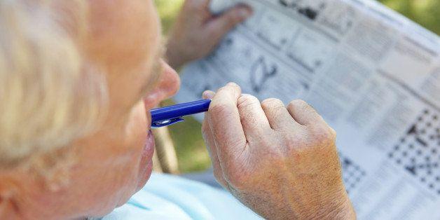 Senior man reading newspaper outside