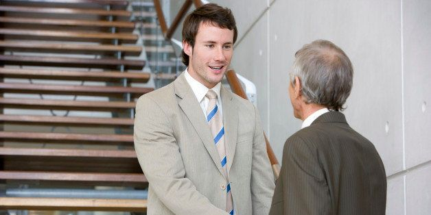 Low angle view of a younger and senior businessman shaking hands. The younger man is standing on a staircase. Vertical shot.