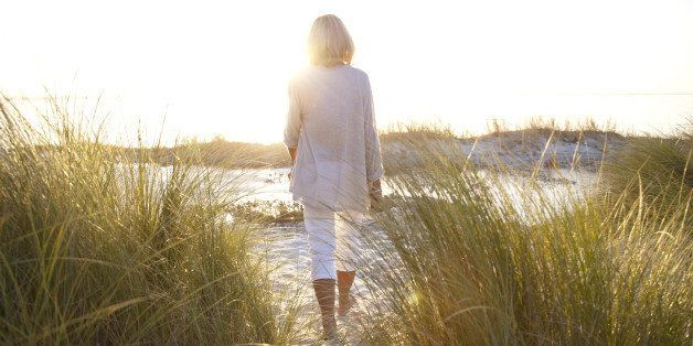 Senior woman, aged 64, walking on a beach at sunset