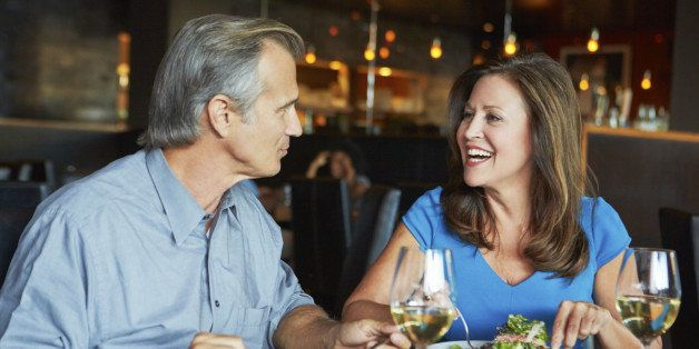 Mature Couple Enjoying Meal At Outdoor Restaurant With Glass Of Wine